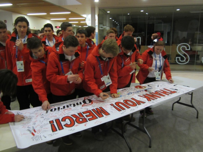 The men's hockey team signing the banner